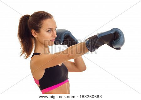 a young girl with the ponytail looks toward and reaches out his hands forward in boxing gloves is isolated on a white background
