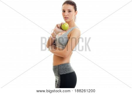 young charming girl looks straight and holding a Green Apple isolated on white background