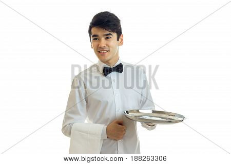 perky young waiter looks to the side and holding a blank tray for eating isolated on white background