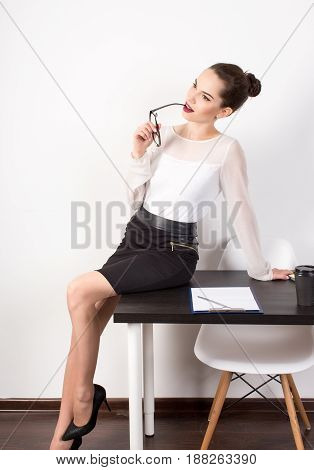 the sexual and thoughtful business woman on a white background sitting on the edge of a desktop at office and looking out of the camera. business people concept.