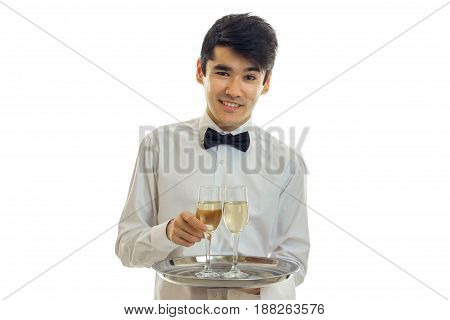 young charming waiter looks straight smiles and holds a tray with two glasses of wine isolated on white background