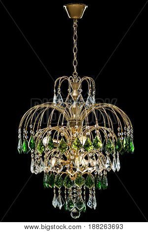 Classic Chandelier for interior decoration of the living room. Large chandelier decorated with green crystals isolated on black background. Gold modern a piece of interior for designers.
