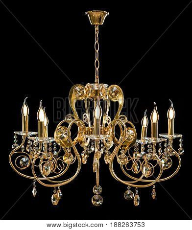 Classic Chandelier for interior decoration of the living room. Large chandelier decorated with crystals isolated on black background. Gold modern a piece of interior for designers.
