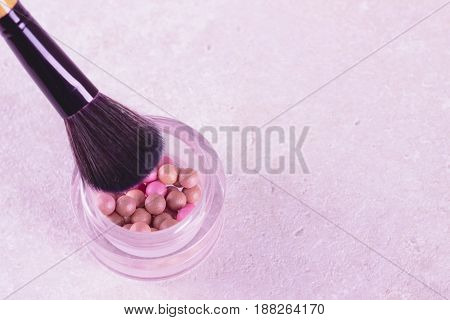 Blush balls in container on textured white background.
