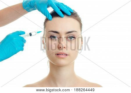 the doctor injects the vaccine on the forehead at young girls without makeup close-up isolated on white background
