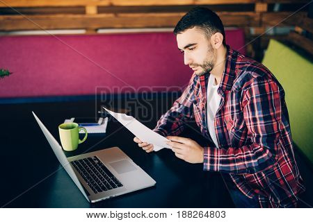Serious Man In Red Shirt Looking At Documents And Sitting  By The Table.