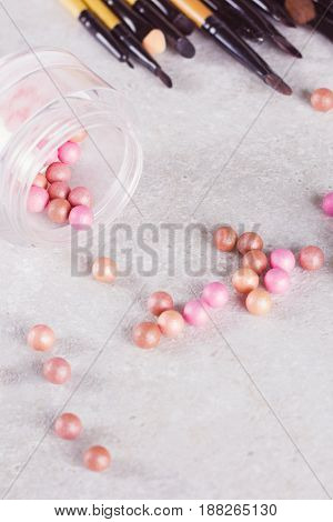 Blush in the balls and make-up brushes close-up.