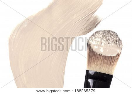 Cosmetic liquid foundation and professional brush isolated on white.