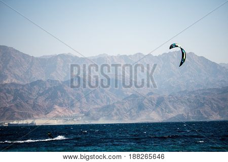 kiter in the surrounding of turquoise sea kiting Israel