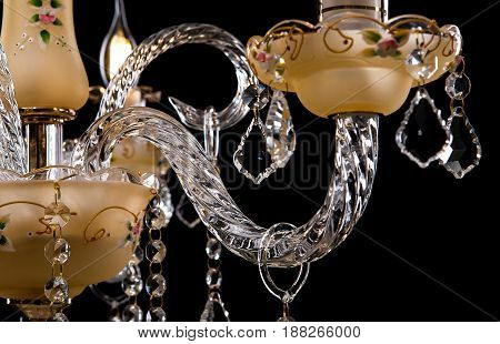 Classic Chandelier for interior decoration of the living room. Large chandelier close-up details decorated with crystals isolated on black background. Gold modern a piece of interior for designers.