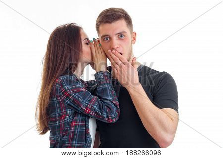 cute girl with long hair whispers a word in the ear of an amazing young guy who closed mouth hand isolated on white