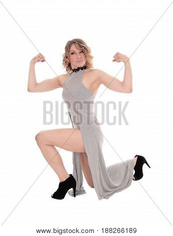 A beautiful blond woman kneeling on the floor in a gray dress and flexing her muscles isolated for white background.