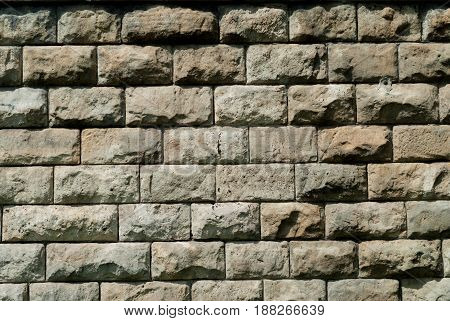 Wall of gray porous stone in brick form