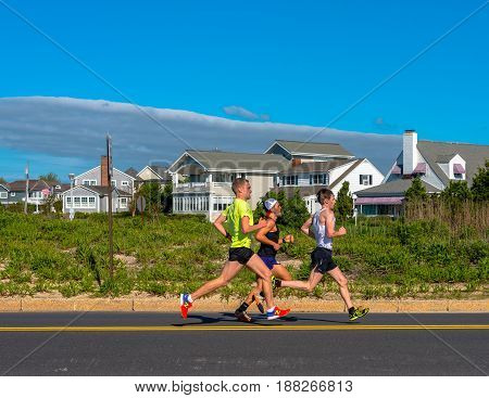 Spring Lake NJ USA -- May 27 2017 Three competitors in the annual Spring Lake 5 mile race sprint down Ocean Avenue. Editorial Use Only.