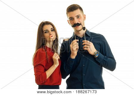 beautiful girl and a young guy hold near face paper Dummies for photo and looking at camera isolated on white background