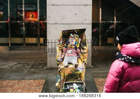 Prague, Czech Republic, December 24, 2016 - A funny clown an adult is disguised as a child in a stroller . Entertainment of tourists in Christmas Europe. Czech Republic
