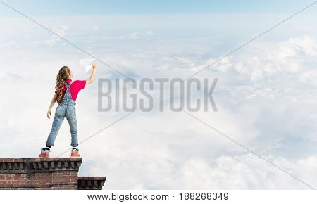 Cute happy kid girl on building top playing with paper plane