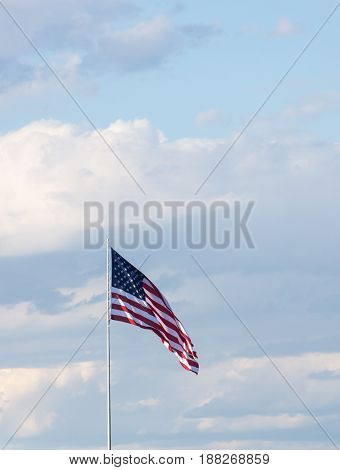 Vertical American flag against a light blue sky with thin clouds. The flag is unfurled in the wind.