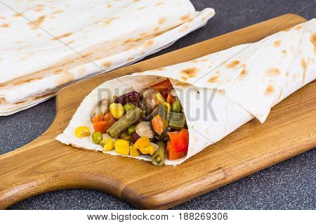 Roll of pita bread with vegetables and mushrooms. Studio Photo