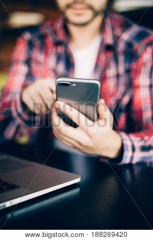 Close Up Of Man In Red Shirt Sitting On Sofa By The Table With Phone