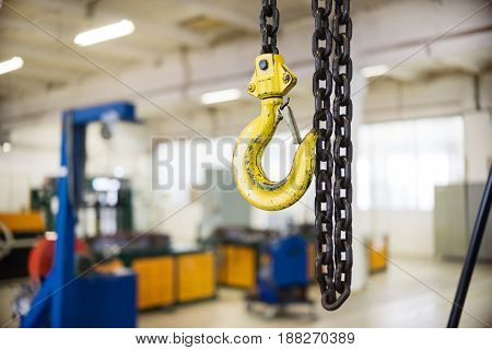 Yellow steel load-lifting hook. Black steel chain.