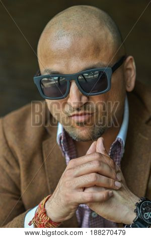 portrait of a hansome indian businessman wearing sunglasses, serious young man thinking.