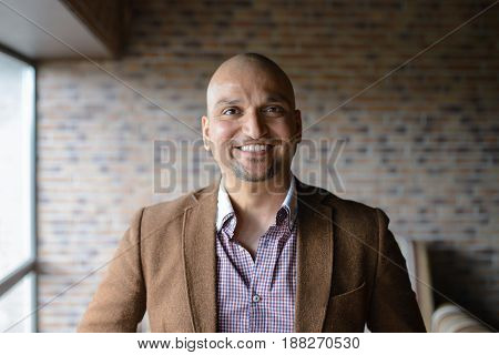 Closeup headshot portrait, happy handsome indian business man, smiling, confident and friendly indoors