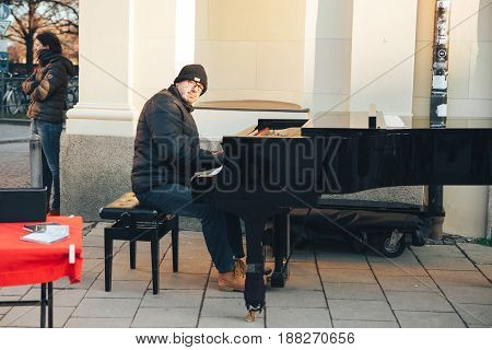 Munich, Germany, December 29, 2016: a street musician playing the piano. Entertainment of tourists in Europe. Street musical performance.