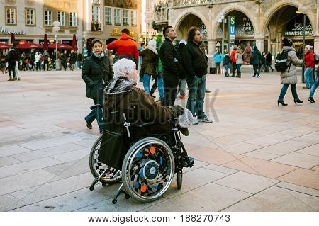 Munich, Germany, December 29, 2016: An elderly woman in a wheelchair examines the sights of Munich on the main square of Marienplatz. Tourist. Access to public places for disabled people.