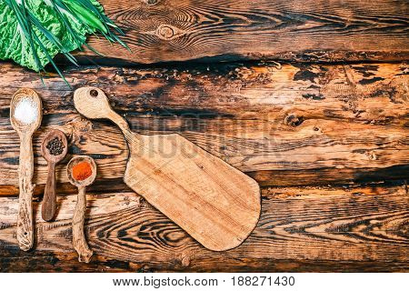 Frame with spices in rustic wooden spoons, seasoning vegetable and cutting board on burned pine wood background