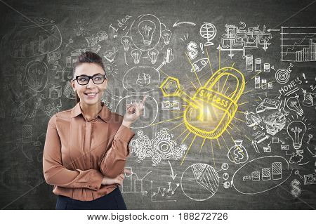 Young businesswoman wearing a brown blouse and glasses is pointing at a business plan sketch and a yellow key to success drawn on a blackboard