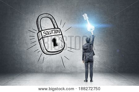 Rear view of a businessman in a dark suit holding a giant key standing near a black wall with a large padlock with a success word on it. Toned image