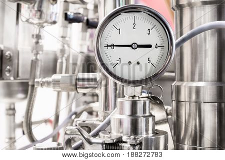 Hydraulic fluid pressure indicator. White dial. Abstract industrial background.