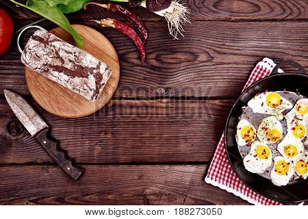 Black cast-iron frying pan with fried quail eggs on a wooden brown background empty space in the middle