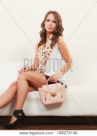 Elegant outfit. Female fashion. Girl in fashionable clothes sitting on sofa with bag handbag