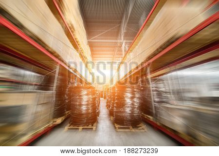 Warehouse industrial and logistics companies. Many boxes packed in a black stretch film. Motion blur effect. Bright sunlight.