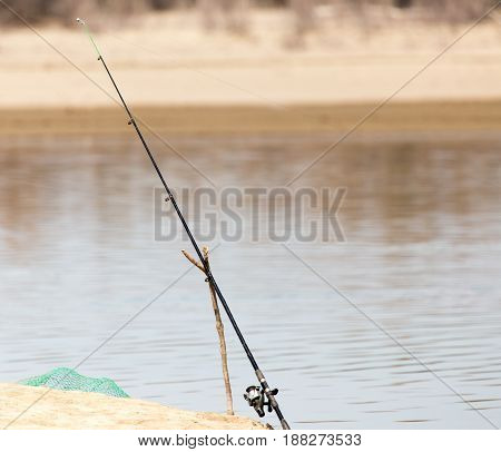 fishing rod on the river bank . A photo