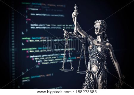 Justice Statue With Code On Monitor Device In Background