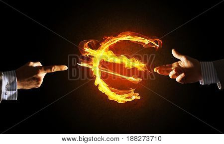 Close of businessman hands pointing at fire glowing euro sign