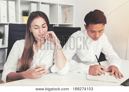 Young Asian businessman is writing in his notebook. His beautiful colleague is looking at her smartphone screen. Toned image