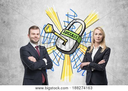 Confident bearded businessman and his beautiful blond colleague standing near a concrete wall with a key to success sketch on it.