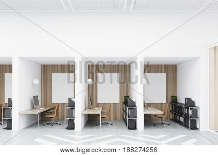 Office cubicles in an office with white and wooden walls and diamond floor pattern. There are blank vertical pictures in each of them a desk with a computer a chair and shelves. 3d rendering mock up