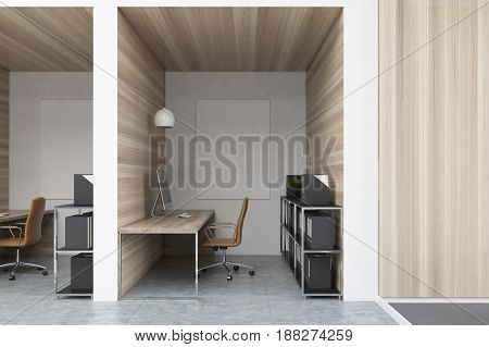 Close up of office cubicles in an office with wooden walls and diamond floor pattern. There are vertical pictures in each of them a desk with a computer a chair and shelves. 3d rendering mock up