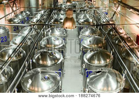 A factory for the production of beer. Rows of glossy metal tanks.