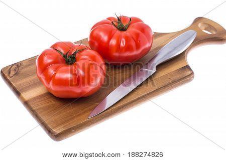 Red tomato on wooden board. Studio Photo