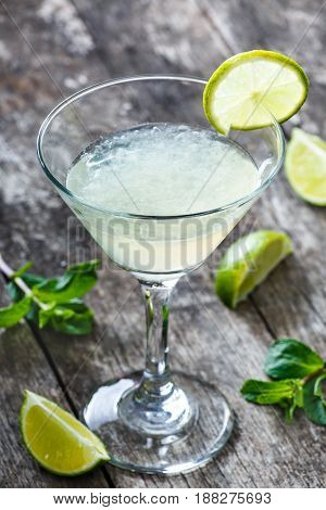 Fresh cocktail with mint and lime in glass on wooden background. Summer drinks and alcoholic cocktails.