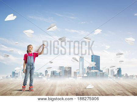 Cute kid girl stand on wooden floor and paper planes flying around