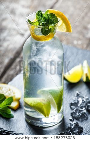 Fresh lemonade mojito with mint lime and ice in glass on wooden background. Summer drinks and alcoholic cocktails.