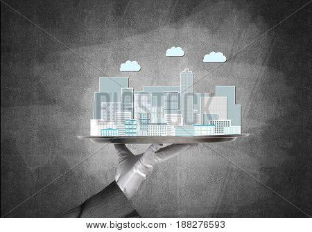 Waiter presenting on tray urban construction sample