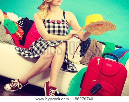 Fashion clothing accessories concept. Woman sitting on sofa in mess wearing checked dress and sneakers holding sun hat.